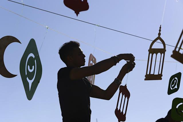 <p>A worker decorates the yard of a coffee shop on the main beach road one day ahead of the holy month of Ramadan, in Gaza City, May 26, 2017. (AP Photo/Adel Hana) </p>