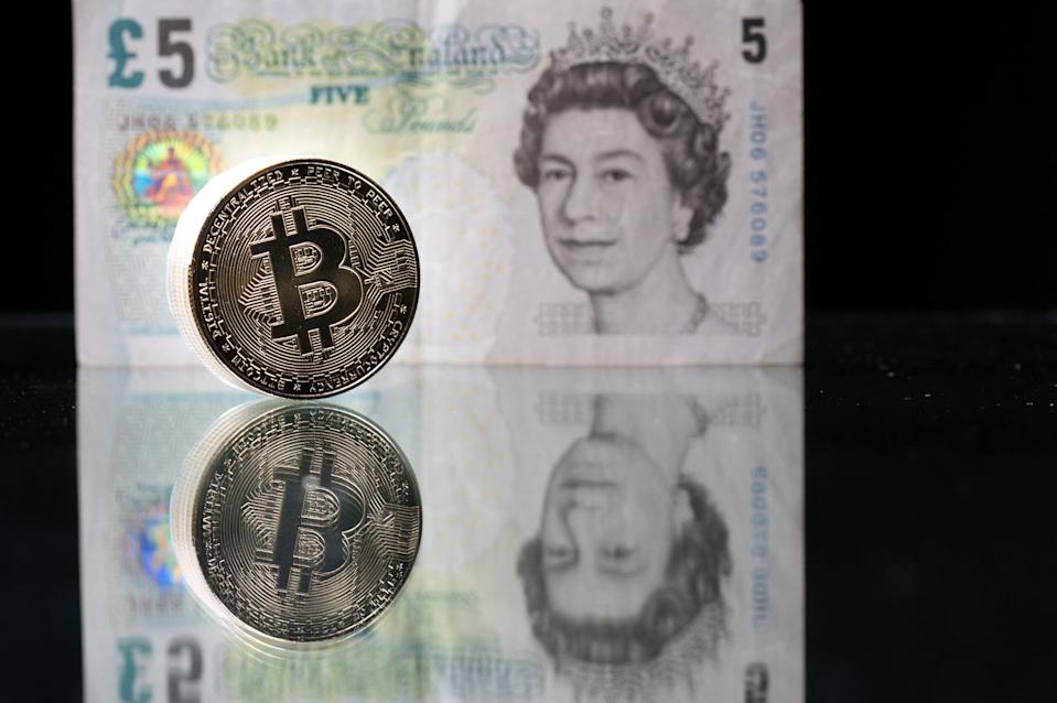 Photo taken in Paris shows a physical imitation of the Bitcoin pictured with a British five pound bank note (AFP via Getty Images)