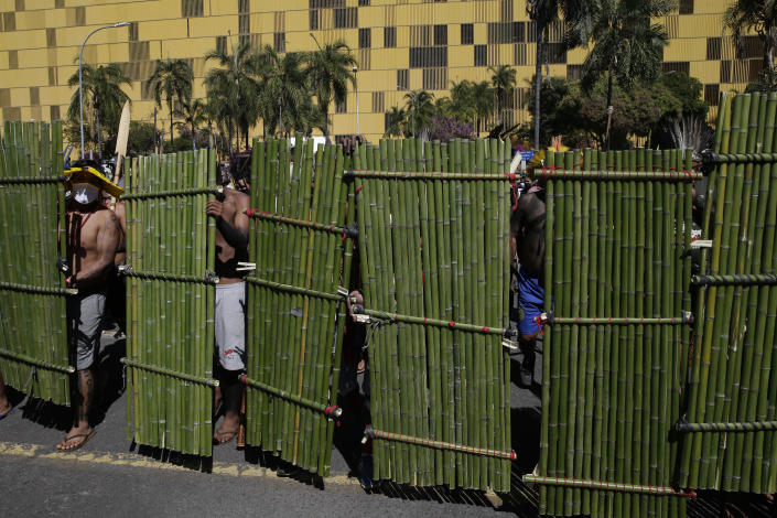 Indigenous with bamboo shields line up outside Congress in Brasilia, Brazil, Tuesday, June 22, 2021. Indigenous are camping in the capital to oppose a proposed bill they say would limit recognition of reservation lands. (AP Photo/Eraldo Peres)