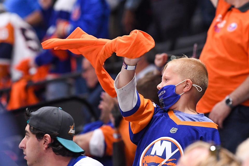 New York Islanders fans cheer in the game against the Pittsburgh Penguins during the third period in Game 6 of the first round of the 2021 Stanley Cup Playoffs at Nassau Veterans Memorial Coliseum.