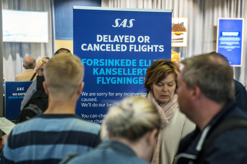 People queue after flights were cancelled by Scandinavian Airlines, at Oslo Airport in Gardermoen, Norway, Friday, April 26, 2019. Pilots for Scandinavian Airlines have launched an open-ended strike following the collapse of pay negotiations, forcing the company to cancel almost all its flights. (Ole Berg-Rusten/NTB Scanpix via AP)