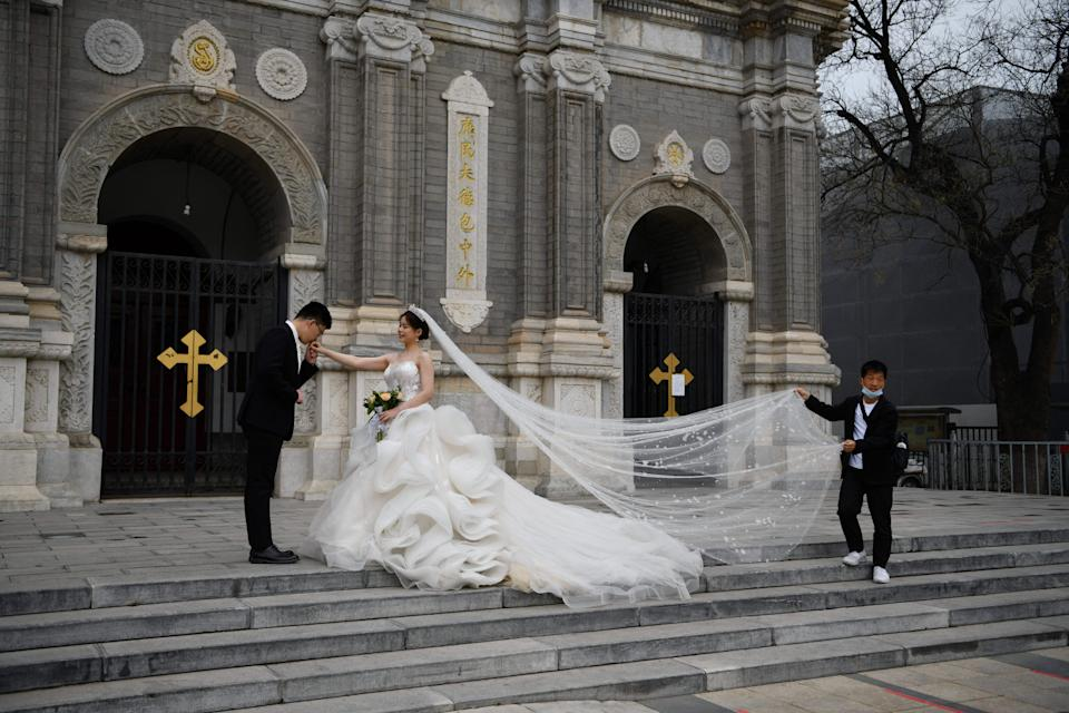 <p>A couple poses for wedding photos outside St Joseph's Church, also known as Wangfujing Catholic Church, in Beijing </p> (AFP via Getty Images)