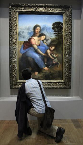 """A man views the newly restored painting """"The Virgin and Child with Saint Anne"""" by Italian Renaissance master Leonardo da Vinci, at the Louvre Museum in Paris, Tuesday, March 27, 2012. A Da Vinci exhibition starts on Thursday with the artpiece """"The Virgin and Child with Saint Anne"""" as the star of a major exhibit exploring the work's genesis, and its place in art history. (AP Photo/Jacques Brinon)"""