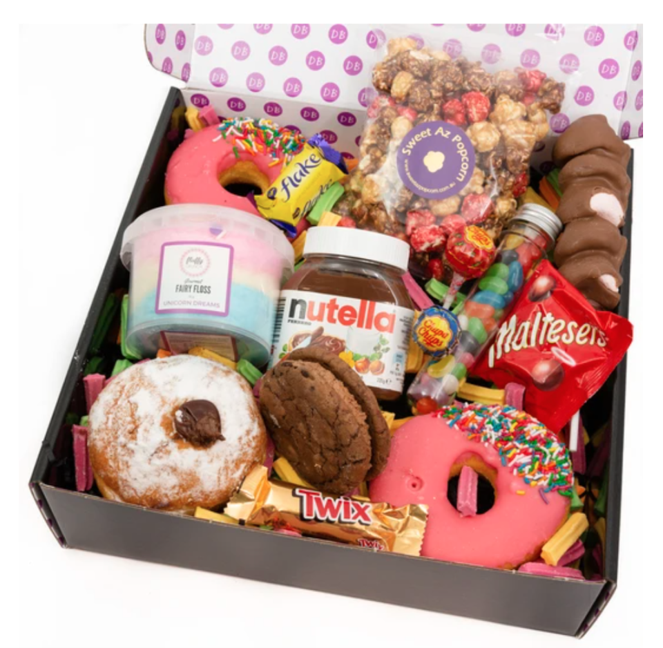 Three donuts wedged in between popcorn, fairy floss and chocolates