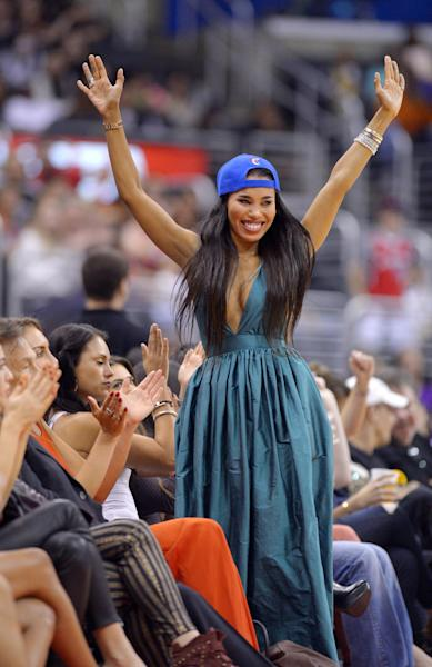 V. Stiviano, center, watches the Los Angeles Clippers play the Sacramento Kings during the first half of their NBA basketball game, Friday, Oct. 25, 2013, in Los Angeles. (AP Photo/Mark J. Terrill)
