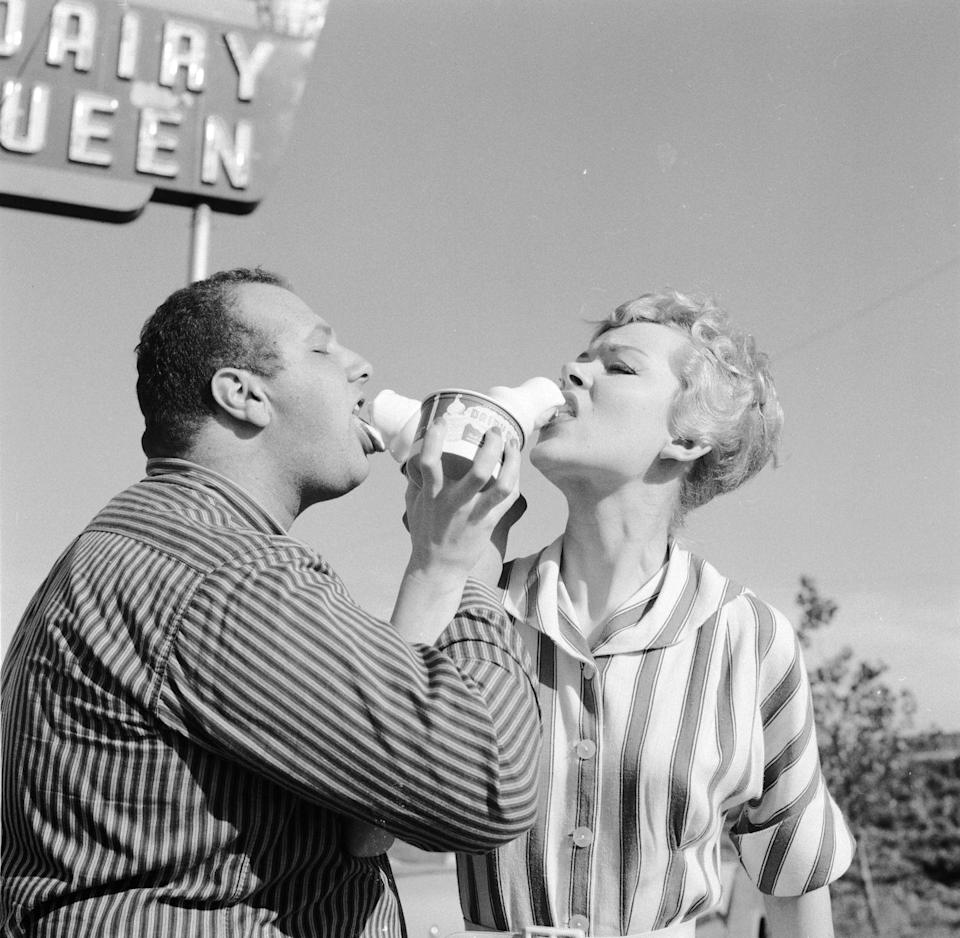 """<p>A couple pose with their ice cream cones outside of a Dairy Queen establishment.</p><p><strong>RELATED: <a href=""""https://www.delish.com/restaurants/g30626323/dairy-queen-vintage-photos/"""" rel=""""nofollow noopener"""" target=""""_blank"""" data-ylk=""""slk:A Look Back At The Evolution of Dairy Queen In Photos"""" class=""""link rapid-noclick-resp"""">A Look Back At The Evolution of Dairy Queen In Photos</a></strong></p>"""