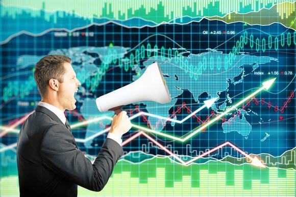 A man in a suit speaks into a megaphone while standing in front of a giant monitor displaying an ascending stock price chart.