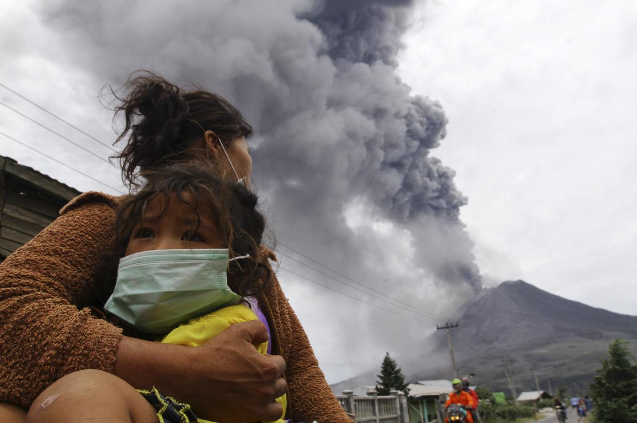 A mother holds her child as Mount Sinabung spews ash and hot lava during an eruption in Perteguhan village in Karo district, Indonesia's north Sumatra province, September 17, 2013. Mount Sinabung threw more volcanic ash into air, covering the surrounding areas on Tuesday, as authorities prepared more temporary shelters for evacuees. REUTERS/Roni Bintang (INDONESIA - Tags: DISASTER ENVIRONMENT TPX IMAGES OF THE DAY)