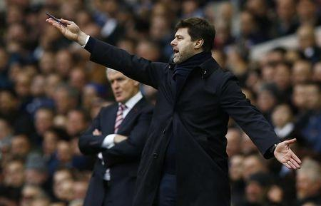 Tottenham manager Mauricio Pochettino gestures during the match as Stoke City manager Mark Hughes looks on
