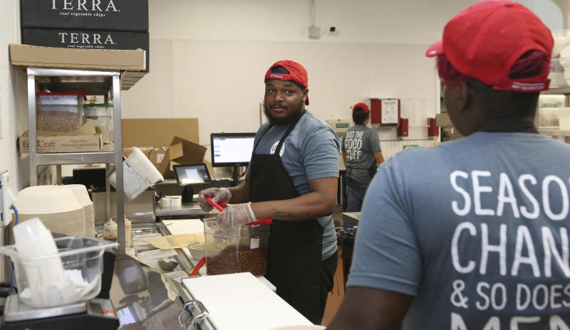 Workers in the B.Good ghost kitchen inside Kitchen United's Chicago, Ill., location prepare food for delivery on Aug. 29, 2019. Kitchen United, a start-up that builds kitchen commissaries for restaurants looking to enter new markets through delivery or take-out only, has plans to open 40 more kitchens in cities across the U.S. through 2020. (AP Photo/Teresa Crawford)