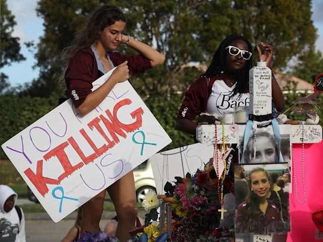<p>Haleigh Grose, a 9th grader at Marjory Stoneman Douglas High School, holds a sign that reads, 'You are Killing Us,' as she visits the memorial setup in front of the school where 17 people that were killed on February 14, on February 21, 2018 in Parkland, Fla. (Photo: Joe Raedle/Getty Images) </p>