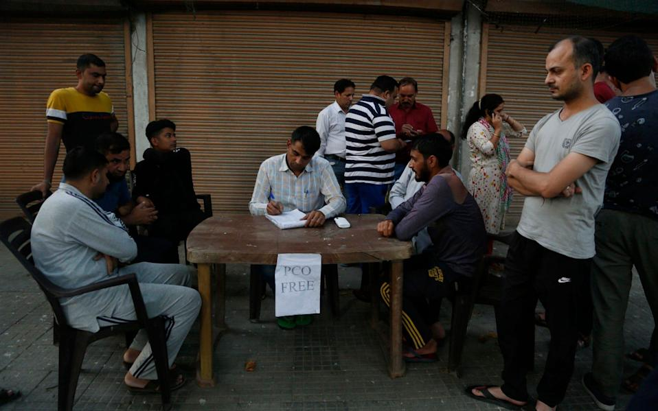 Kashmiri men registers his number before making a call from a free public telephone provided by Indian paramilitary soldiers for civilians outside their base camp after a communications blackout