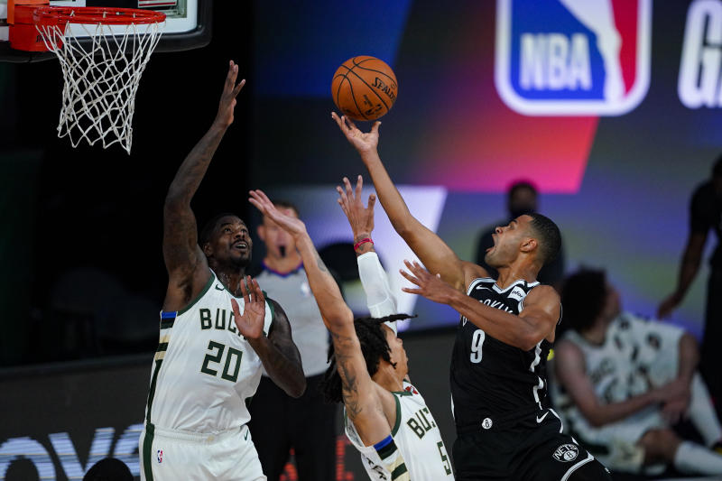Brooklyn Nets guard Timothe Luwawu-Cabarrot (9) shoots over Milwaukee Bucks forward Marvin Williams (20) and forward D.J. Wilson (5). (AP Photo/Ashley Landis)