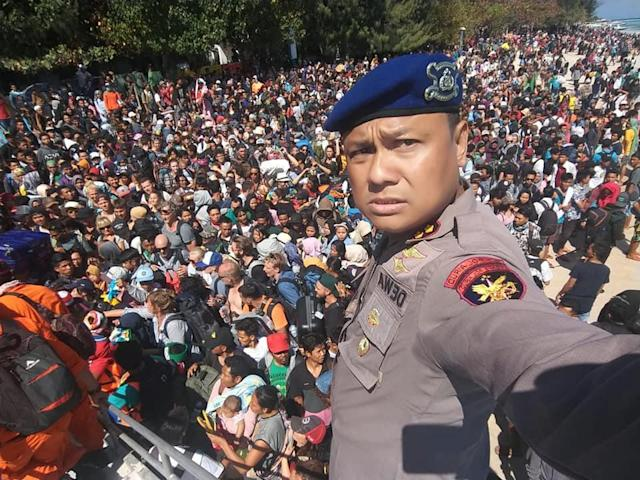 <p>Chief Water Police of Lombok Dewa Wijaya takes a picture in front of hundreds of people attempting to leave the Gili Islands after an earthquake Gili Trawangan, in Lombok, Indonesia, Aug. 6, 2018, (Photo: Indonesia Water Police/Handout via Reuters) </p>