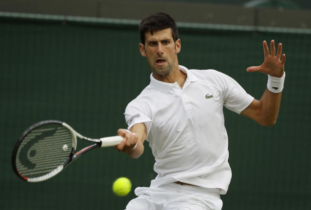 Novak Djokovic of Serbia returns the ball to Karen Khachanov of Russia during their men's singles match on the seventh day at the Wimbledon Tennis Championships in London, Monday July 9, 2018. (AP Photo/Kirsty Wigglesworth)