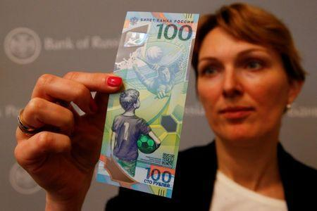 FILE PHOTO: An employee holds the newly designed 100-rouble banknote dedicated to the 2018 FIFA World Cup, during a news conference in Moscow, Russia May 22, 2018. REUTERS/Sergei Karpukhin/File Photo
