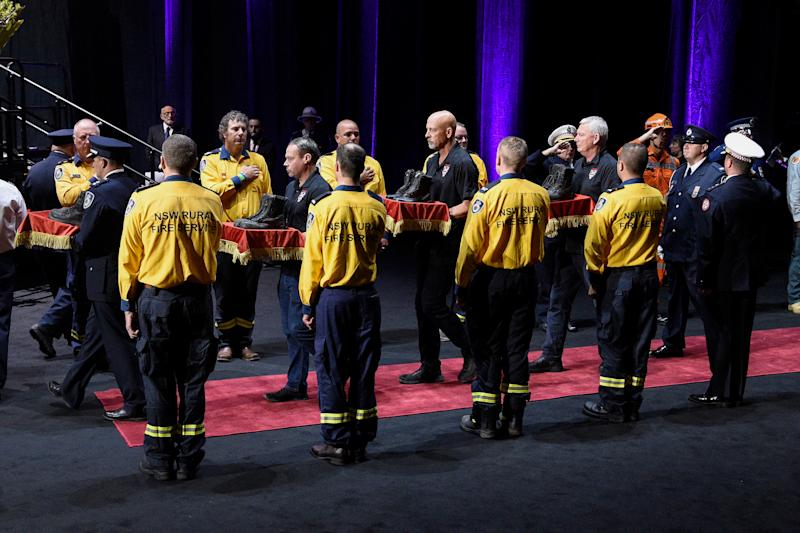 Fire boots representing the six RFS and Coulson Aviation firefighters killed in the recent bush fires are carried through a guard of honour at the Bushfire State Memorial at Qudos Bank Arena in Sydney, Sunday, February 23, 2020. (AAP Image/Bianca De Marchi) NO ARCHIVING