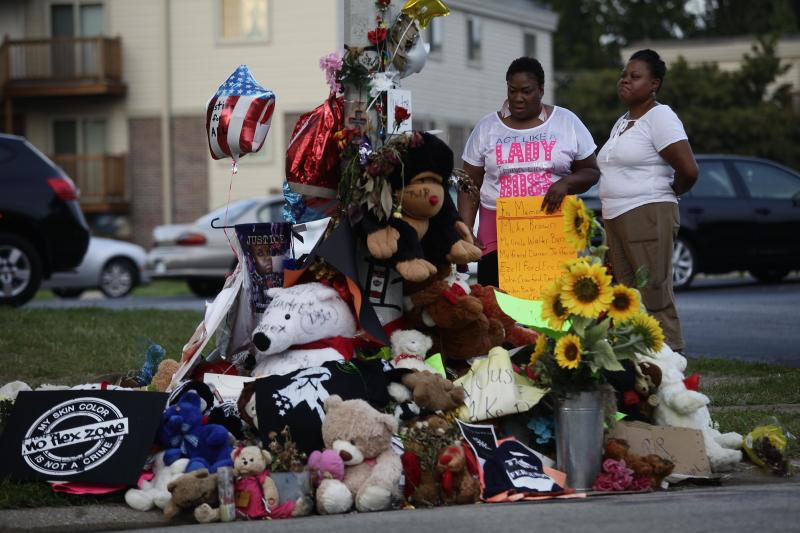 Two woman stand over a makeshift memorial to Michael Brown on August 22, 2014 in Ferguson, Missouri (AFP Photo/Joshua Lott)