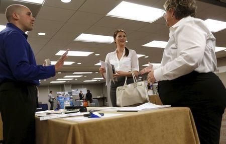 Kathleen Blake (C), who said she is seeking a job in sales, is greeted by prospective employers during a job hiring event for marketing, sales and retail positions in San Francisco, California June 4, 2015.  REUTERS/Robert Galbraith