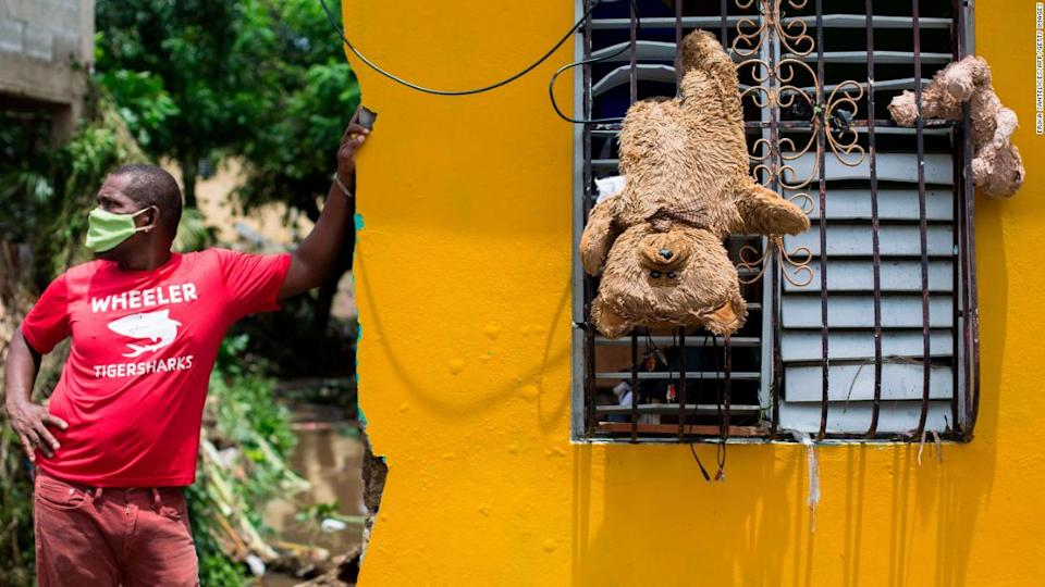 """<p>A man remains outside his home, where teddy bears hang from a window to dry after the passage of the storm throuth Hato Mayor, Dominican Republic, on July 31, 2020.</p><div class=""""cnn--image__credit""""><em><small>Credit: Erika Santelices/AFP/Getty Images / Getty</small></em></div>"""