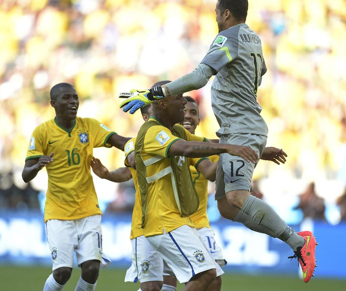 Brazil's goalkeeper Julio Cesar leaps into his teammates arms after a penalty shoot out during the World Cup round of 16 soccer match between Brazil and Chile at the Mineirao Stadium in Belo Horizonte, Brazil, Saturday, June 28, 2014. Brazil won 3-2 on penalties after a 1-1 tie. (AP Photo/Manu Fernandez)