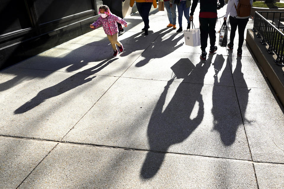 Shoppers cast their shadows Saturday, Nov. 28, 2020, as they walk Chicago's famed Magnificent Mile shopping district while a young kid runs by. (AP Photo/Charles Rex Arbogast)