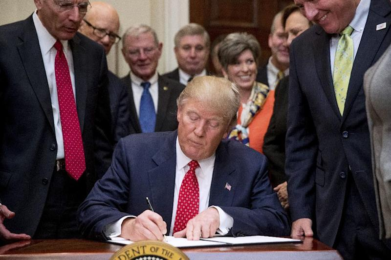 President Donald Trump signs the Waters of the United States (WOTUS) executive order, Tuesday, Feb. 28, 2017, in the Roosevelt Room in the White House in Washington, which directs the Environmental Protection Agency to withdraw the Waters of the United States (WOTUS) rule, which expands the number of waterways that are federally protected under the Clean Water Act. (AP Photo/Andrew Harnik)