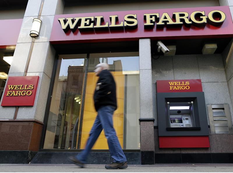 FILE - In this Wednesday, Dec. 19, 2012, file photo, a man walks past a Wells Fargo location in Philadelphia.  Wells Fargo, the biggest U.S. mortgage lender, says it earned a record $4.9 billion in the fourth quarter, up 25 percent from the same period a year before. Revenue rose 7 percent, to $21.9 billion, beating the $21.3 billion expected by analysts polled by FactSet. (AP Photo/Matt Rourke, File)
