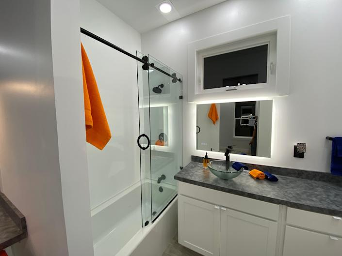 the bathroom with a shower, sink, mirror