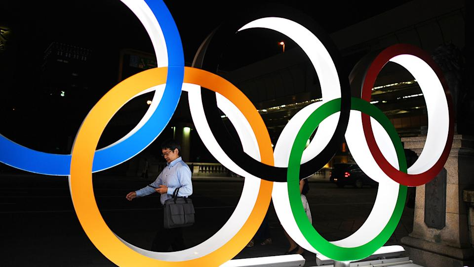 A man, pictured here walking in front of the Olympic Rings in Tokyo.