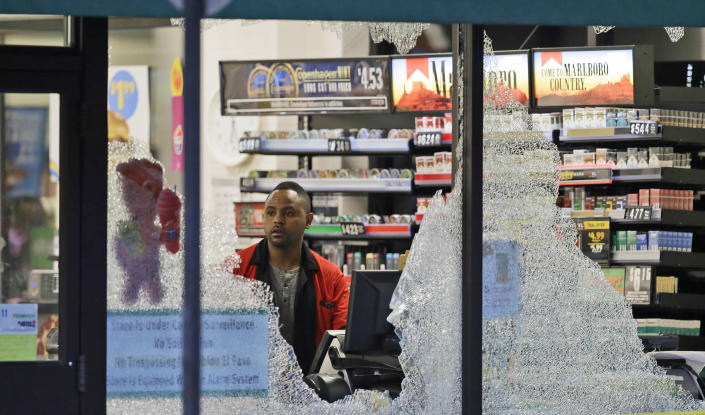 <p>A clerk looks at broke windows shot out at a store in downtown Dallas, July 8, 2016. Snipers opened fire on police officers in the heart of Dallas during protests over two recent fatal police shootings of black men. (Photo: LM Otero/AP) </p>
