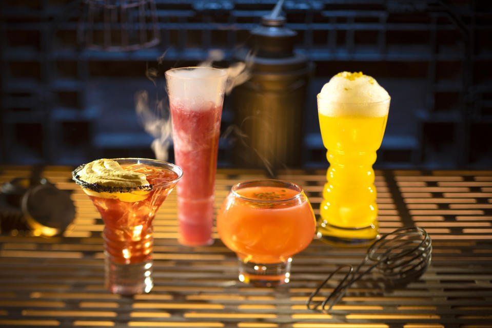 """Non-alcoholic drinks found at Oga's Cantina include, left to right, the Carbon Freeze, Oga's Obsession and the Cliff Dweller. The Cliff Dweller is named as a <a href=""""https://www.yahoo.com/entertainment/star-wars-galaxy-edge-food-secrets-inside-disneyland-disney-world-galactic-menu-212455244.html"""" data-ylk=""""slk:tribute to Porgs;outcm:mb_qualified_link;_E:mb_qualified_link;ct:story;"""" class=""""link rapid-noclick-resp yahoo-link"""">tribute to Porgs</a>. (Photo: Kent Phillips/Disney Parks)"""