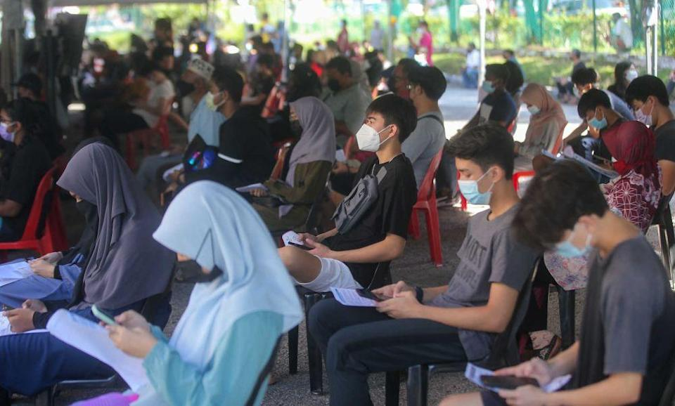Student wait to receive their Covid-19 jab at the Kinta Town Hall in Batu Gajah September 21, 2021. — Picture by Farhan Najib