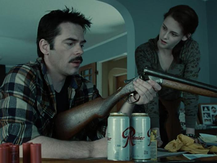 """Billy Burke (Charlie Swan) cleans his gun while Bella (Kristen Stewart) watches over his shoulder in a scene from """"Twilight."""""""
