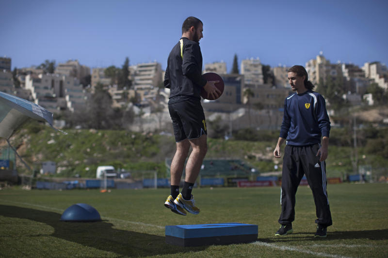 Beitar Jerusalem F.C. soccer player Zaur Sadayev, left, train in Jerusalem, Friday, Feb. 8, 2013. The offices of the Beitar Jerusalem soccer team were set on fire early Friday in an apparent arson attack, police said, a day after four of the club's fans were charged with anti-Muslim chanting at a recent game. Tensions have been bubbling ever since the team announced last month it would sign on two Muslim Chechen players — Zaur Sadayev and Gabriel Kadiev — in a break from the team's unofficial tradition of not signing Arabs or Muslims. (AP Photo/Bernat Armangue)