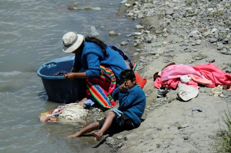 A woman washes clothes on the banks of the Keka river in Achacachi