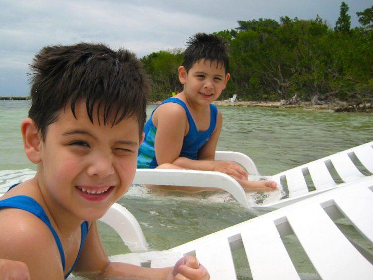Twin boys enjoying water play activity in a lake
