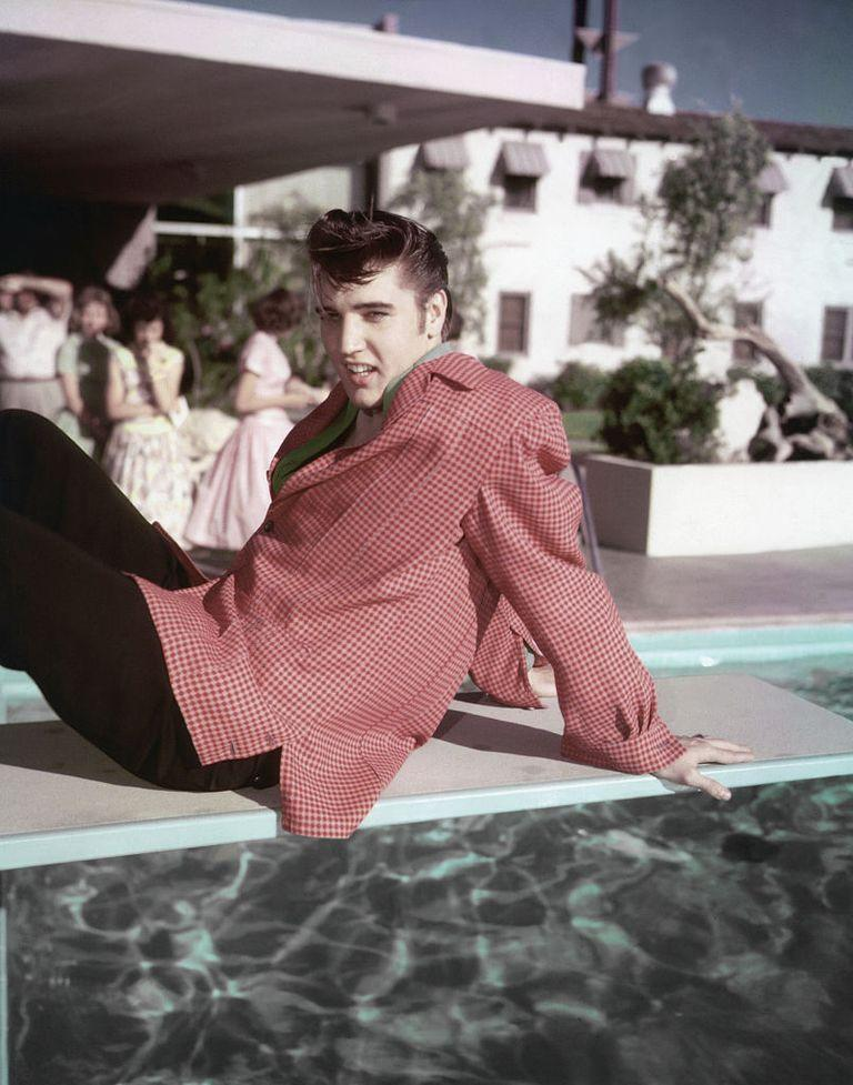 <p>Elvis Presley wears a red checkered sport coat as he reclines on the Frontier Hotel's diving board in Las Vegas in 1955. </p>