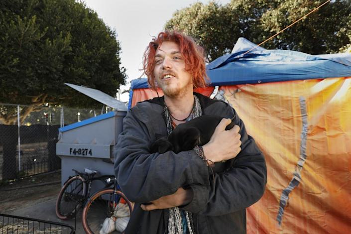 A man holds a black puppy outside a tent