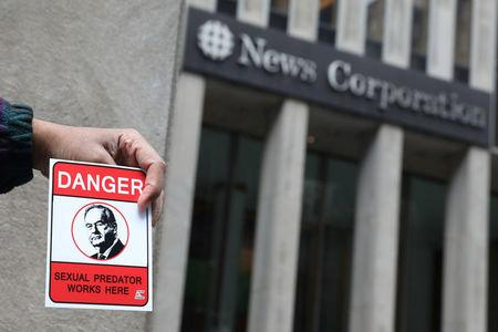 A man who said he was hired displays fliers opposing Bill O'Reilly outside the News Corporation headquarters in New York. REUTERS  Shannon Stapleton