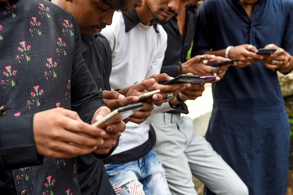 In this photo taken on November 10, 2019, youngsters watch videos on video-sharing app TikTok on their mobile phones in Mumbai. - He's no Bollywood superstar, but Israil Ansari can barely walk down a street in India without teenagers flocking to him for autographs -- thanks to TikTok, the addictive and controversial app on which he has two million followers. (Photo by Indranil MUKHERJEE / AFP) (Photo by INDRANIL MUKHERJEE/AFP via Getty Images)