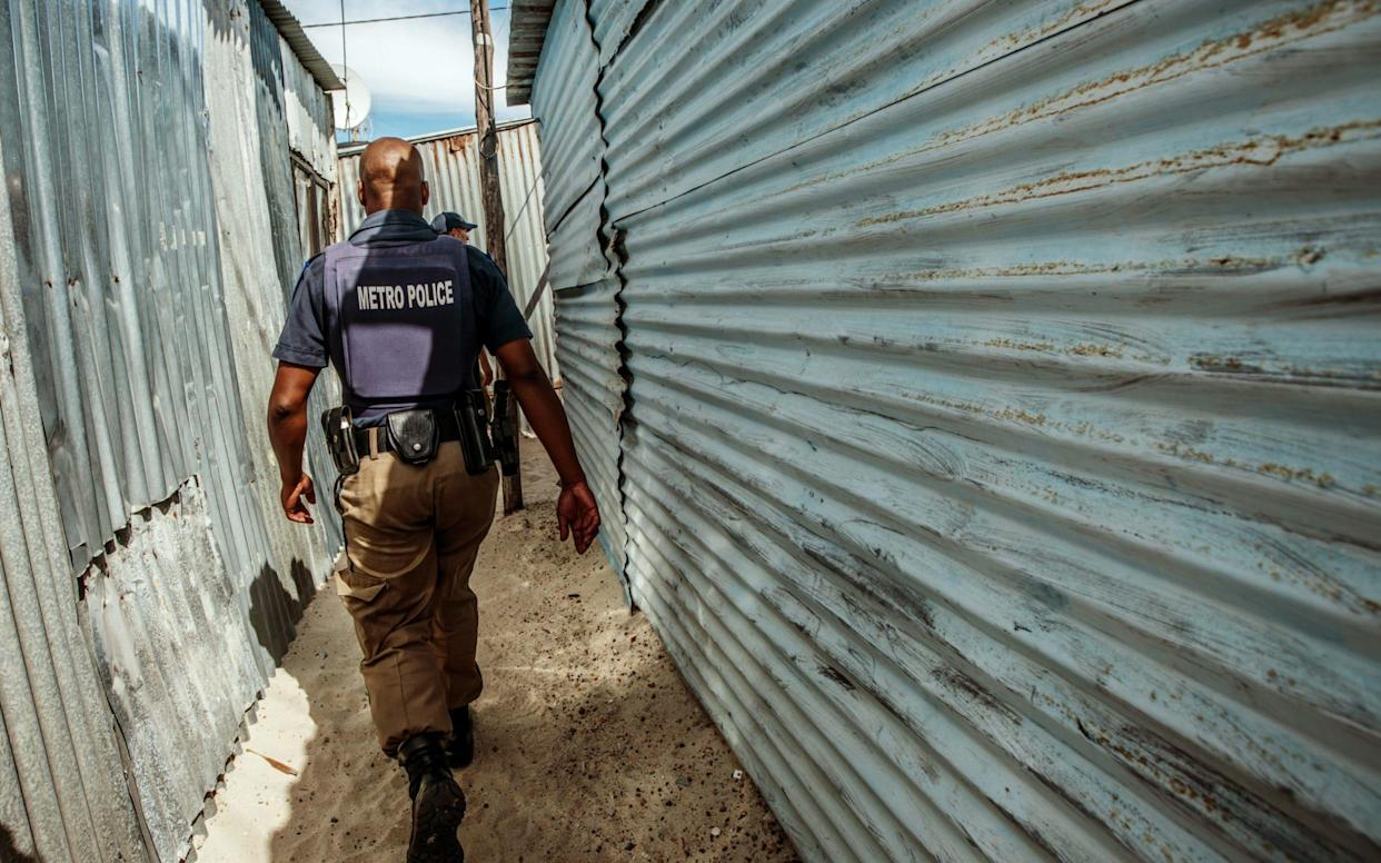 Law enforcement agents move through the Cape Flats township  - Getty Images Europe