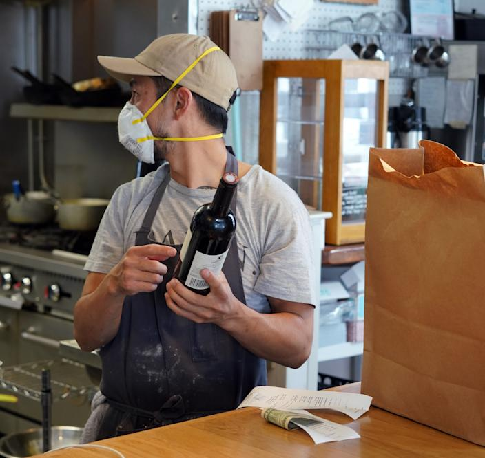 Chef Kris Hammond of The Regional in Fort Collins, Colo. , wears an N-95 mask in the kitchen as he inspects wine sold to a takeout customer.