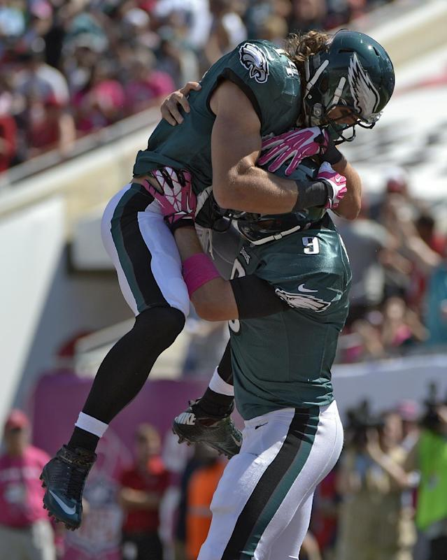 Philadelphia Eagles quarterback Nick Foles (9) celebrates with wide receiver Riley Cooper (14) after Foles scored on a four-yard touchdown run against the Tampa Bay Buccaneers during the first quarter of an NFL football game Sunday, Oct. 13, 2013, in Tampa, Fla. (AP Photo/Phelan M. Ebenhack)