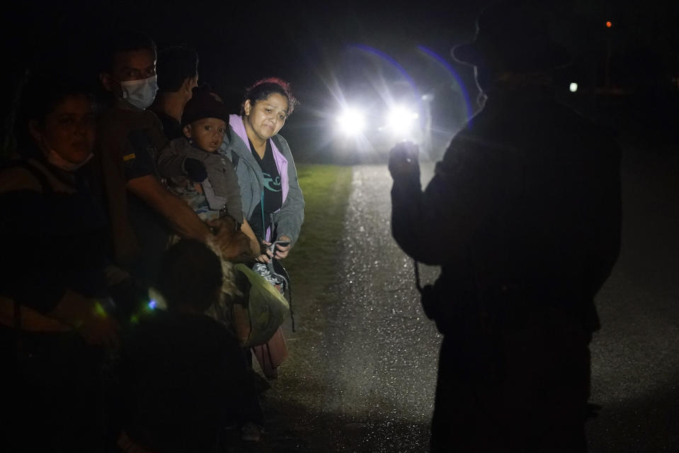 Migrants mainly from Honduras and Nicaragua stand in line after turning themselves in upon crossing the U.S.-Mexico border Monday, May 17, 2021, in La Joya, Texas. The Biden administration has agreed to let up to about 250 people a day in the United States at border crossings with Mexico to seek refuge, part of negotiations to settle a lawsuit over pandemic-related powers that deny migrants a right to apply for asylum, an attorney said Monday. (AP Photo/Gregory Bull)