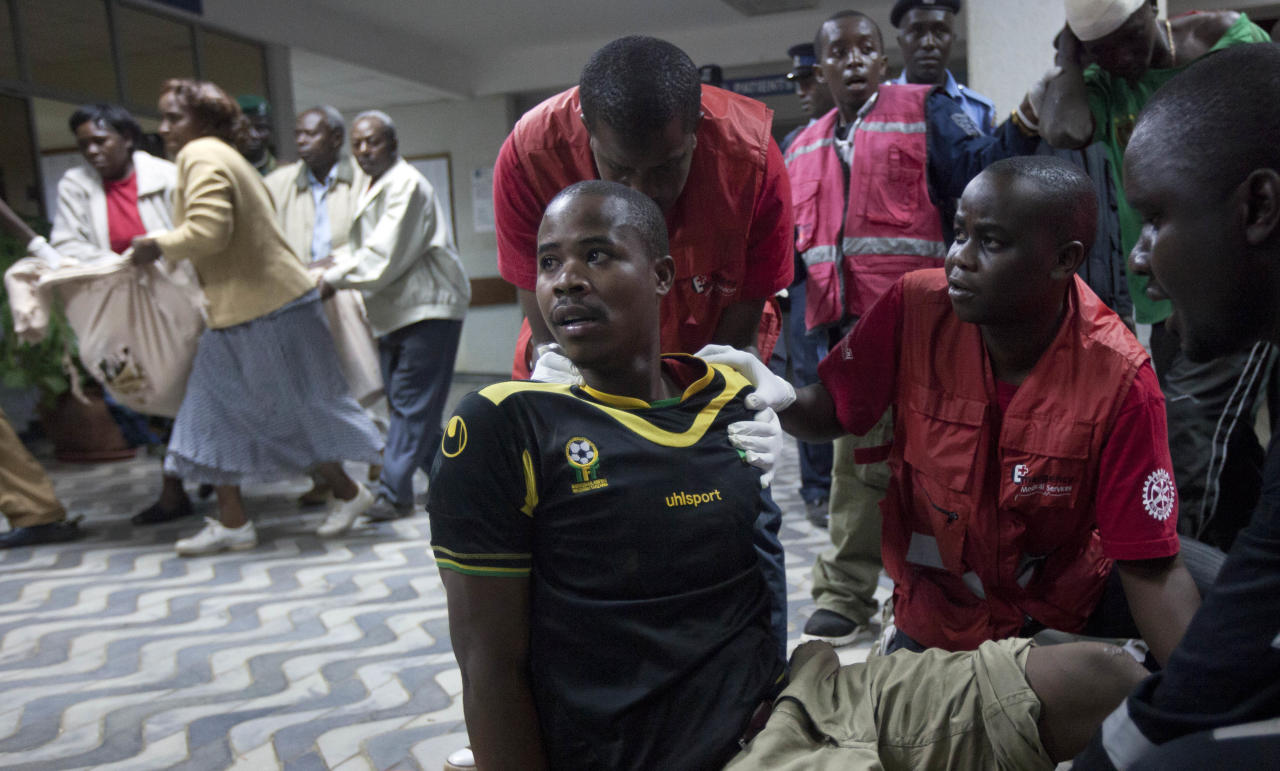 A man injured in a grenade attack at a downtown bus station sits on the floor after falling out of the ambulance and looks across as other wounded arrive, one carried in a bed sheet, left, at Kenyatta Hospital in Nairobi, Kenya Saturday, March 10, 2012. Explosions at one of the Kenyan capital's main bus terminals killed at least two people and left two dozen others wounded Saturday, officials and witnesses said. (AP Photo/Ben Curtis)
