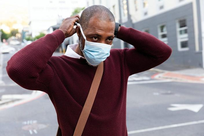 African American man wearing red pullover, out and about in the city streets during the day, putting on a face mask against air pollution and covid19 coronavirus.