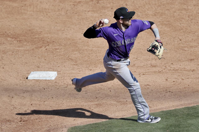 Colorado Rockies' Trevor Story throws out Chicago Cubs' Willson Contreras at first during the third inning of a spring training baseball game against the , Tuesday, Feb. 25, 2020, in Mesa, Ariz. (AP Photo/Matt York)