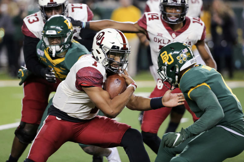 Oklahoma quarterback Jalen Hurts, left, carries the ball as Baylor cornerback Jameson Houston, right, defends during the second half of an NCAA college football game in Waco, Texas, Saturday, Nov. 16, 2019. (AP Photo/Ray Carlin)