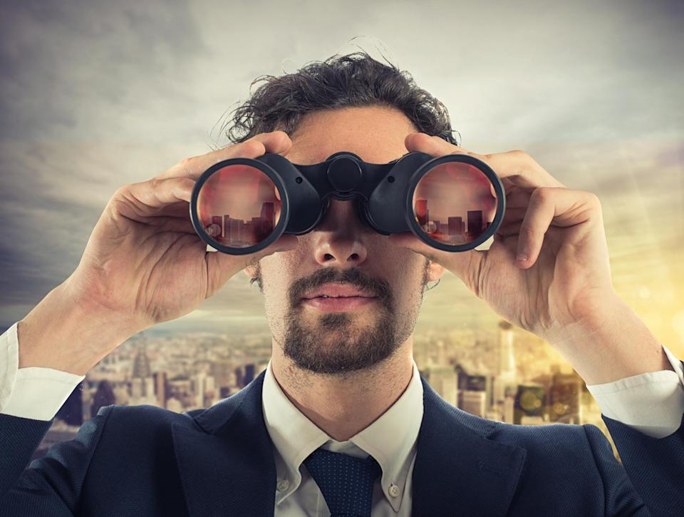 Guy in a suit looking through binoculars with a city behind him.